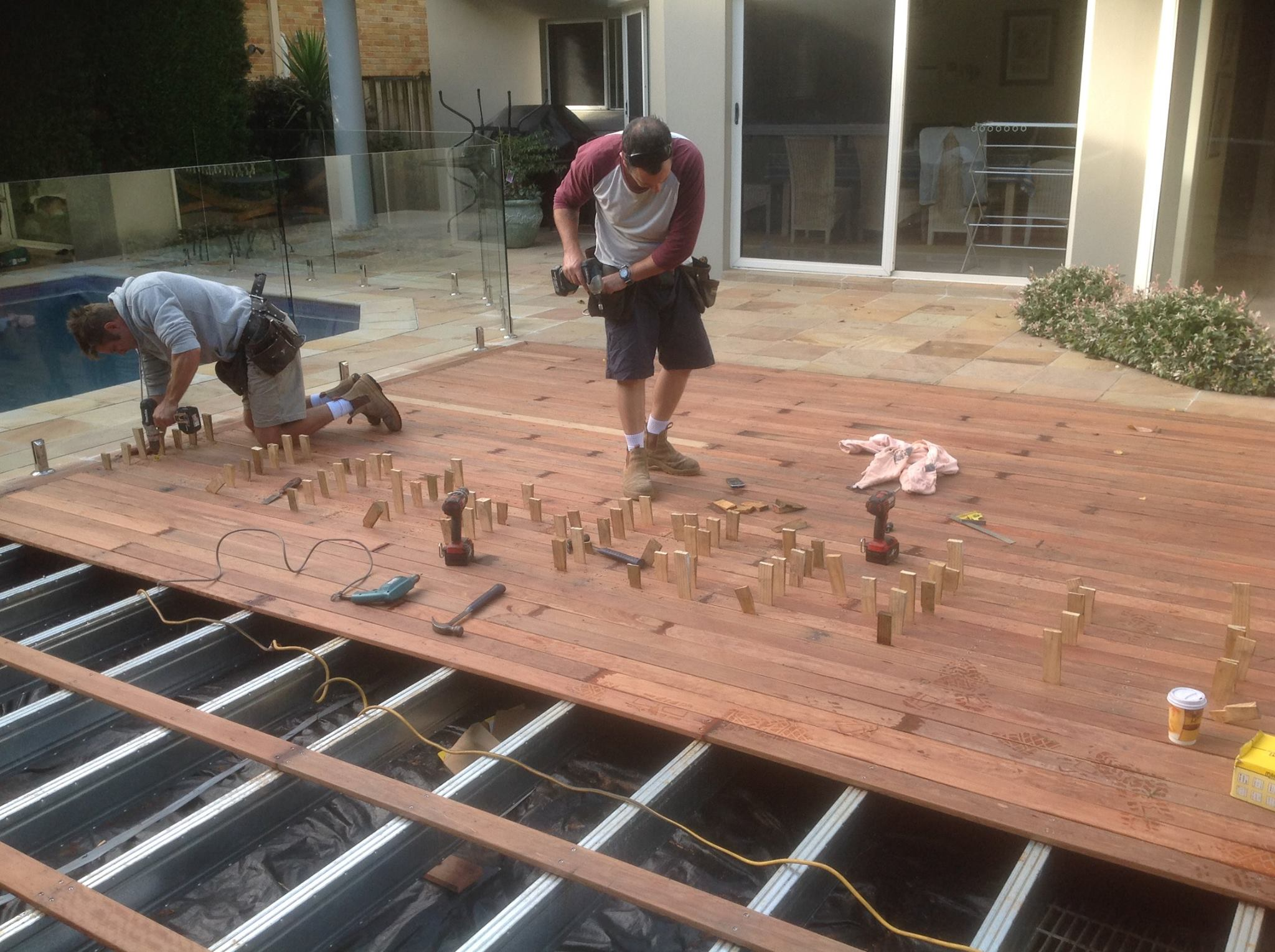 Two men fixing decking boards to a steelframe deck next to a pool. The bearers and joists are Boxspan extra protective coating hot dip galvanised HDG beams.