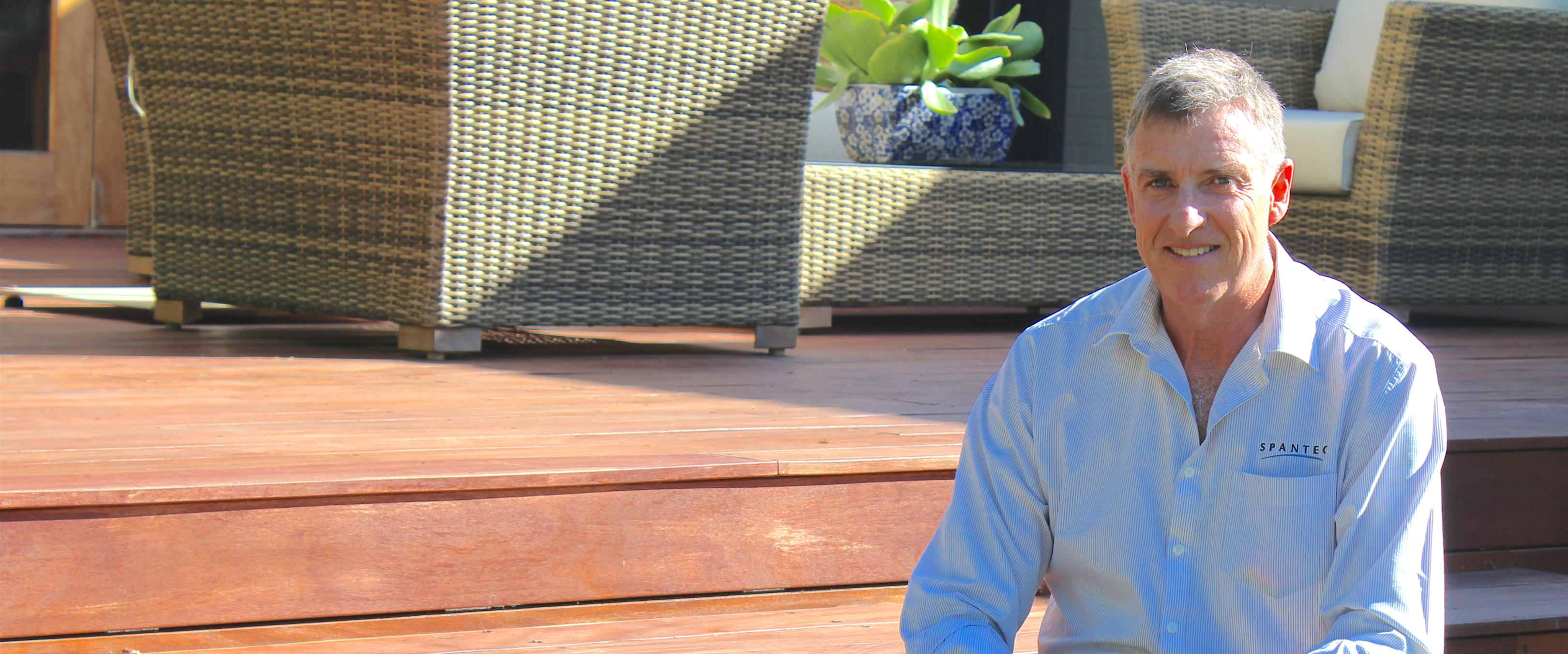 Spantec Director, Roy Beaumont smiling, witting on a deck constructed using Spantec deckframe.