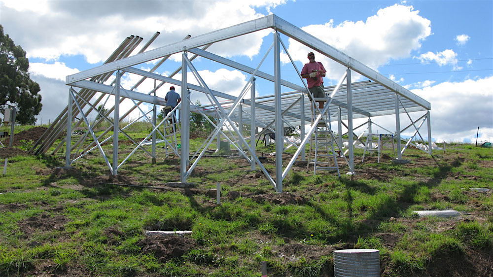 A Boxspan floor frame under construction with Ezipier and crossbracing with owner-builder Bill con a ladder on the slopey block of land