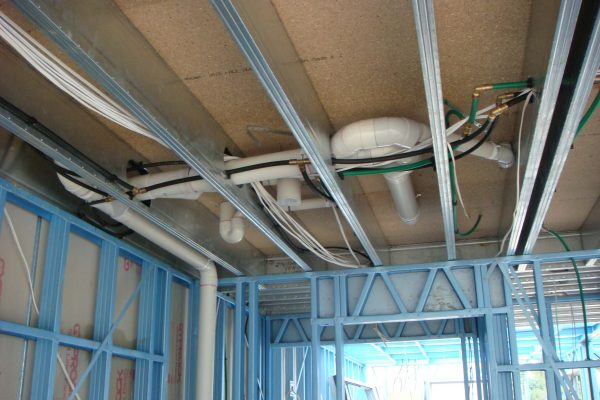Boxspan upper floor frame beams with service holes for plumbing and electrical cables