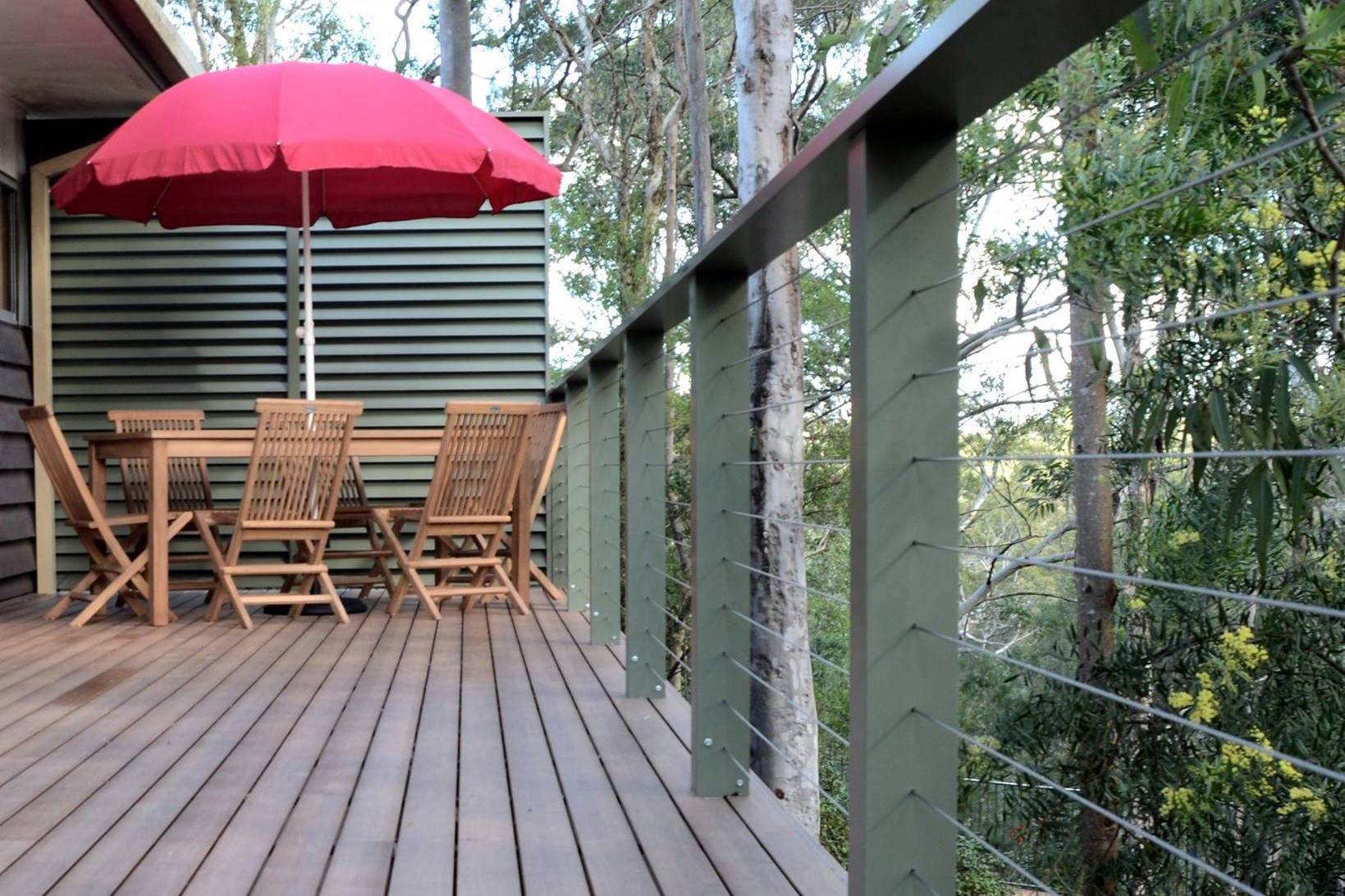 A deck of steel Boxspan frame and aluminium decking powdercoated in timber look in a bushland setting with a table, chairs and umbrella on it.