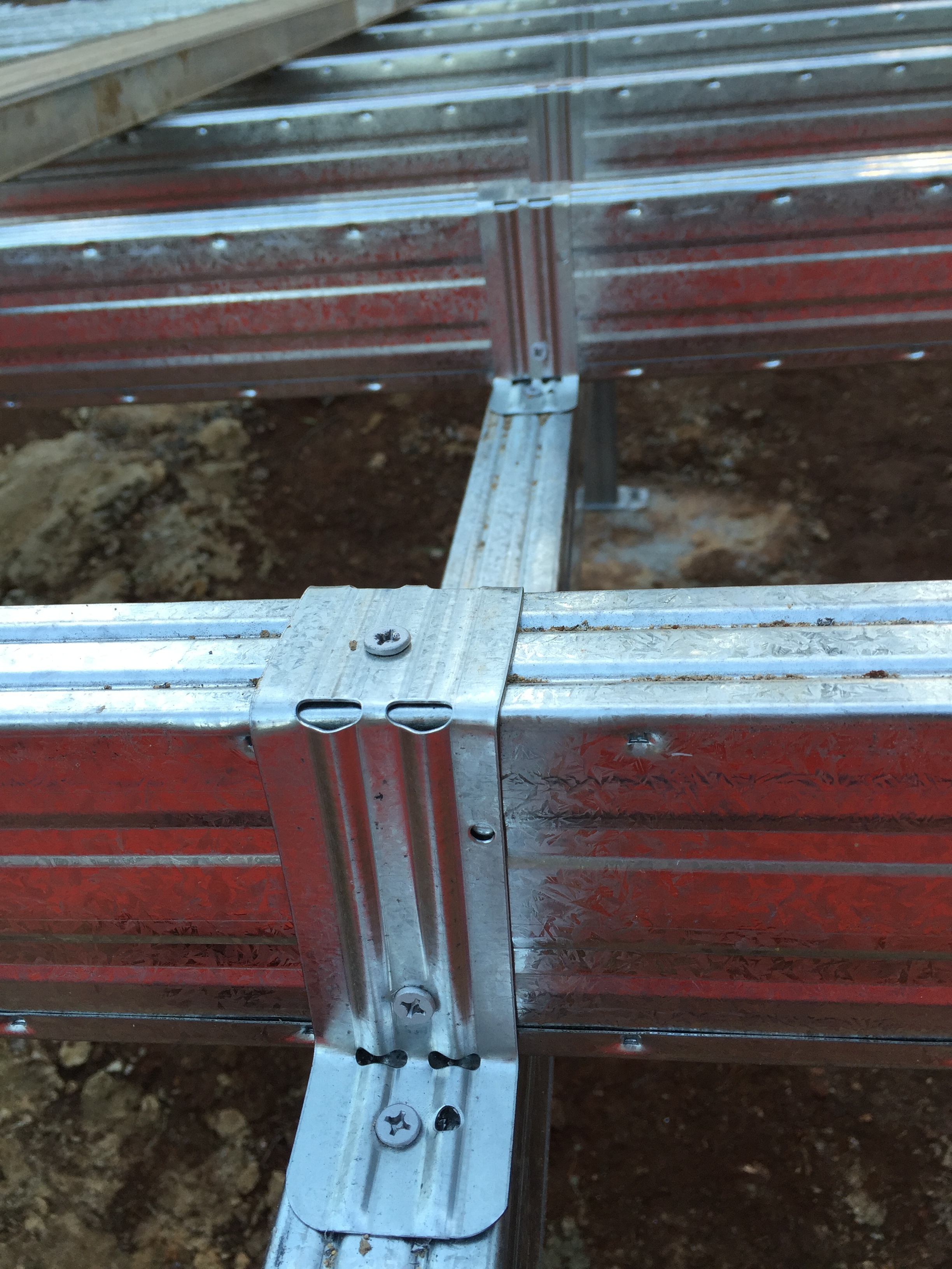 Boxspan steel floor subframing completed, close up view of the top hat brackets attaching the joists to the bearers.