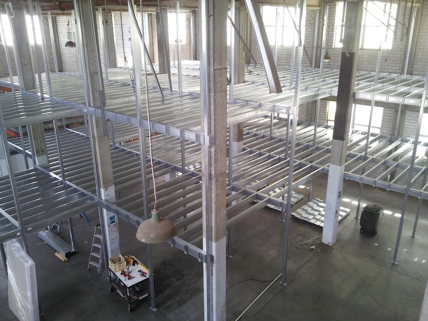 Boxspan mezzanine floor frames in a factory space for storage lockers.