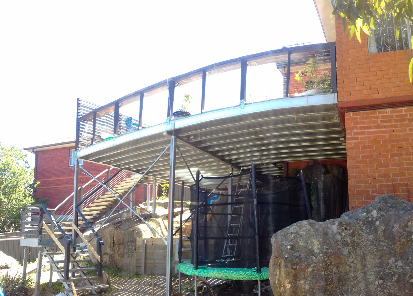 Deck built on a challenging steep sloping site straddling boulders underneath it