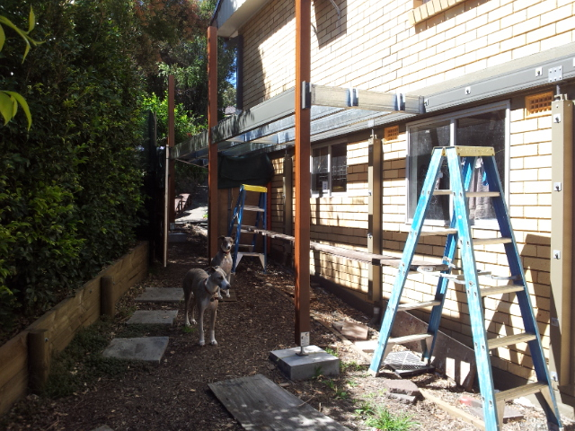 Elevated covered walkway being built using a Boxspan frame attached to an existing house