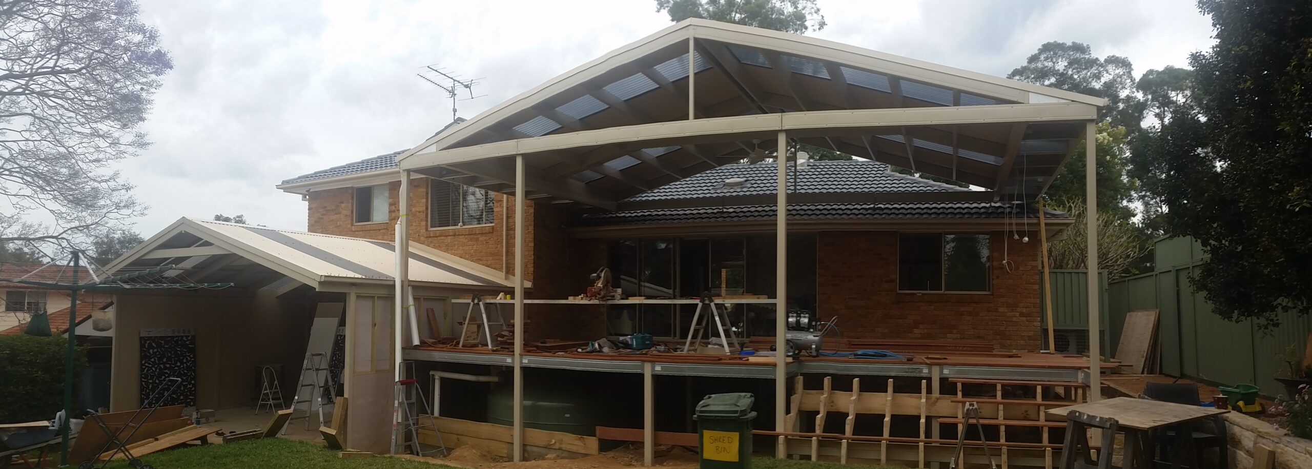Boxspan Deck and pergola framing complete, stairs under construction, frame added to existing house